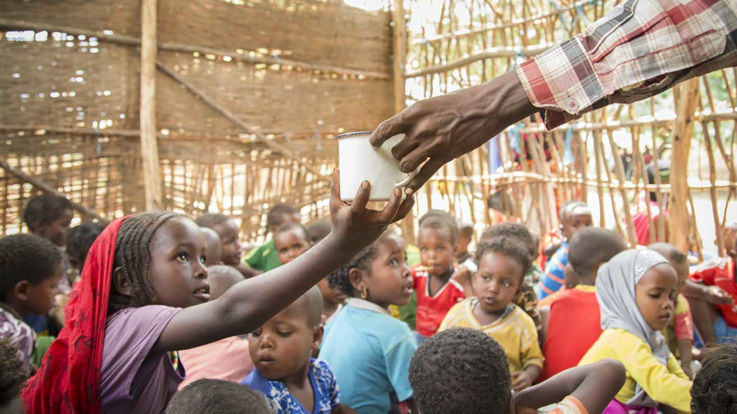 Misra (6) receives a cup of water during meal time at a ChildFund-supported early childhood development center in Fentale District, Ethiopia. May 8, 2017. Photo by Jake Lyell for ChildFund.
